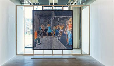 A large fresco painting by Rosie Hastings and Hannah Quinlan of women fighting hangs on a wooden frame covering the width of the room. Daylight comes